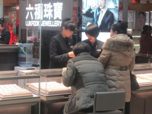 圖片2:專櫃職員細心為顧客介紹飾品_副本