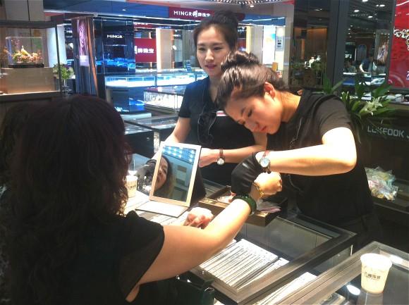 圖片2:專櫃職員悉心為顧客佩戴飾品